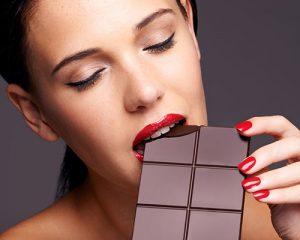 mujer con labios rojos mordiendo una barra de chocolate