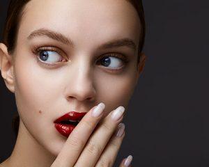 mujer con mano en boca y uñas largas
