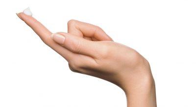 mano con gota de crema en el dedo