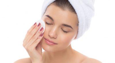 mujer limpiando la cara con algodon