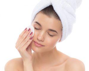 Mujer limpiandose la cara con algodon
