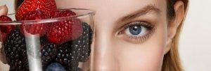 Mujer con un vaso lleno de moras y frutos rojos