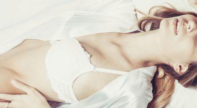 Mujer dormida en una cama blanca