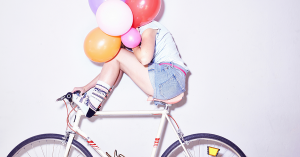 Mujer en bicicleta con globos