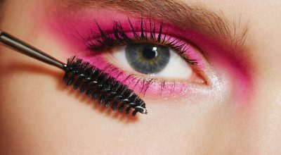 Ojos con fondo rosa poniendo rímel