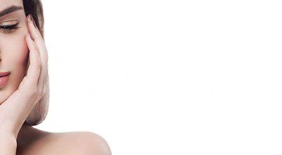 mujer con fondo blanco sobandose la cara