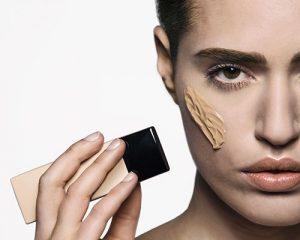 mujer aplicándose base de maquillaje