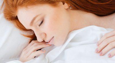 Mujer dormida en la cama con el pelo suelto