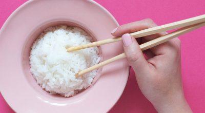 Palillos chinos con arroz y mano