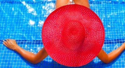 mujer con sombrero sentada en una alberca