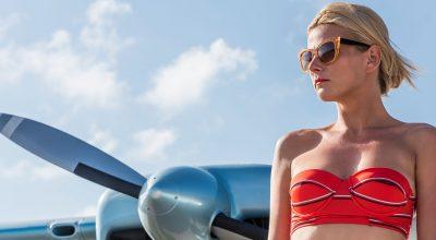 mujer con traje de dos piezas y avión en el fondo