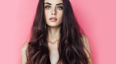 mujer con pelo largo y fondo rosa