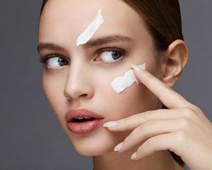 Mujer poniendose crema en la cara