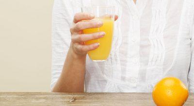 Mujer con un vaso de jugo de naranja