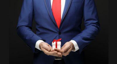Hombre con traje y caja de regalo en mano