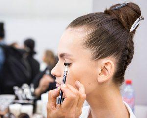mujer siendo maquillada de los ojos