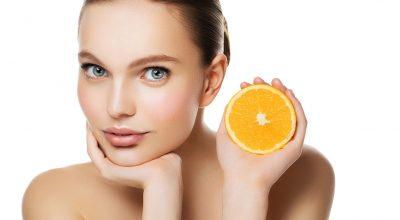 mujer con naranja en mano